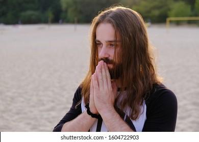 ハンサムなひげを生やした男性が街の背景にナマステポーズで手で祈る