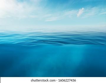 Blaue Meer- oder Ozeanwasseroberfläche und Unterwasser mit sonnigem und bewölktem Himmel