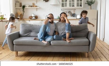 La madre y el padre cansados que se sientan en el sofá se sienten molestos y agotados mientras la hijita y el hijo ruidosos corren alrededor del sofá donde los padres descansan. Niños hiperactivos demasiado activos, necesitan concepto de reposo