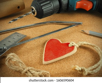 Wooden red heart on cord surrounded by tools - jigsaw, screwdriver, ruler and pencil, on cork surface. Handmade gift. Valentine's day, Women's day, Birthday concept.