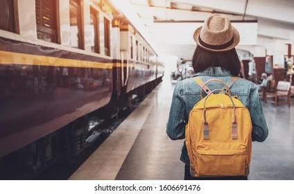 鉄道のバックパック、旅行者と駅でバックパックと帽子、旅行の概念を持つ若いアジアの女性旅行者。駅を歩く女性旅行者観光客