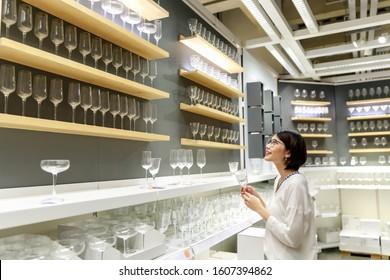 Joven asiática de pelo corto hermosa mujer eligiendo copas de vino para comprar en la tienda de gafas de muebles