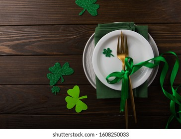 St. Patrick's Day green Shamrocks with fork, spoon, and napkin on rustic brown wood board background with room or space for copy, text, words. Square