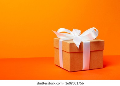 Trendy attractive minimalistic gift on the orange background. Merry Christmas, St. Valentine's Day, Happy Birthday and other holidays concept.