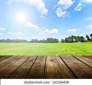 背景の青い空と空の木製デッキテーブル。製品表示モンタージュの準備ができています。