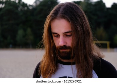 Close up, Portrait of a handsome Caucasian bearded young man with long flowing hair in the sunset river. Man in despair