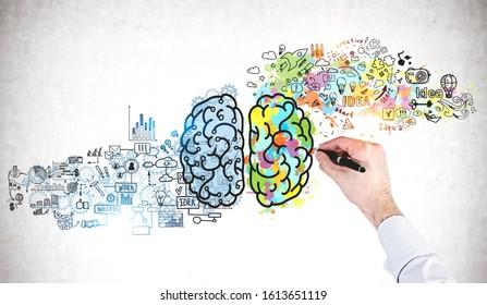 Mano de hombre de negocios dibujo dibujo colorido cerebro en muro de hormigón. Concepto de pensamiento creativo y lluvia de ideas
