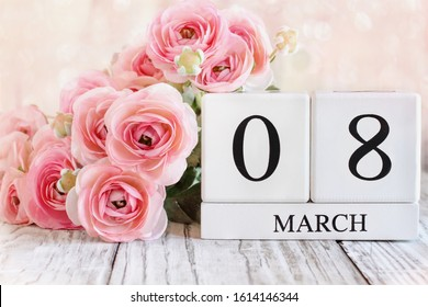 White wood calendar blocks with the date March 08 for International Women's Day and pink ranunculus flowers over a wooden table.