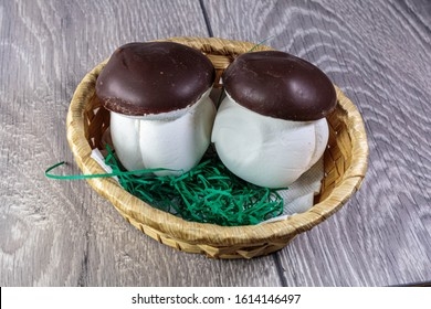 Mushrooms from white marshmallow with chocolate hat. Marshmello boletus in a wicker basket.