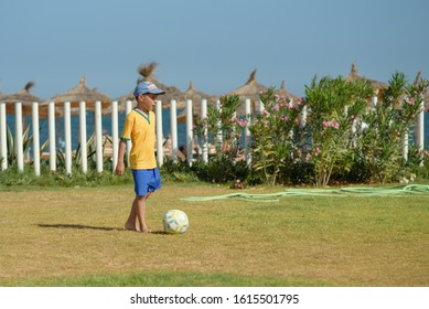 Young football player on the green field during his summer vacations. He is playing football.