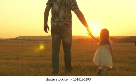 子供は父親と一緒に牧草地で花を摘みます。小さな娘は手をつないで牧草地でお父さんと一緒に歩きます。子供は父親の手を握ります。家族は夕方に町を出て歩きます。お父さんと赤ちゃんは公園で休んでいます。