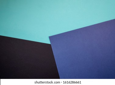Abstract colored paper geometry background minimalist concept, flat lay top view, multicolored empty image with copy space for any design purposes, dark blue, light blue, simple black