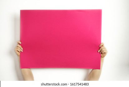 A large sheet of red paper in hands on a white background. Copy space. Woman hold blank card.