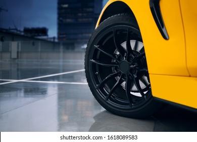 Rueda delantera y llantas de coche deportivo moderno. Reflexión de coche en un piso de concreto húmedo de estacionamiento
