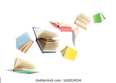 Libros de tapa dura coloridos volando sobre fondo blanco.