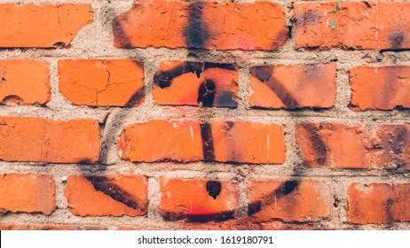 Ojo pintado con pintura negra sobre una pared de ladrillos
