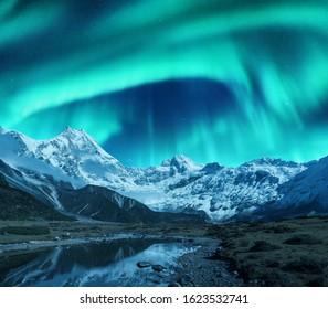 Aurora borealis über den schneebedeckten Bergen, der Küste des Sees und dem Spiegelbild im Wasser. Nordlichter über schneebedeckten Felsen. Winterlandschaft mit Polarlichtern, See. Sternenhimmel mit heller Aurora