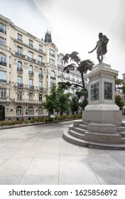 View of the Plaza de las Cortes with statue of famous Spanish poet Miguel de Cervantes and to the building Plus Ultra Seguros in Madrid, Spain
