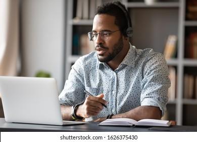 Fokussierte junge afrikanische Geschäftsmann tragen Kopfhörer Studie online ansehen Webinar Podcast auf Laptop hören Lernen Bildung Kurs Konferenzschaltung machen Notizen am Schreibtisch sitzen, E-Learning-Konzept