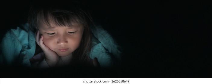 夜のベッドで光の点滅でタブレットを見て、女の子が画面から反射したり、電話を使用したり、タブレットゲームや漫画中毒のスマートフォンconcepts.wideバナーを遊んでいる子供たち。