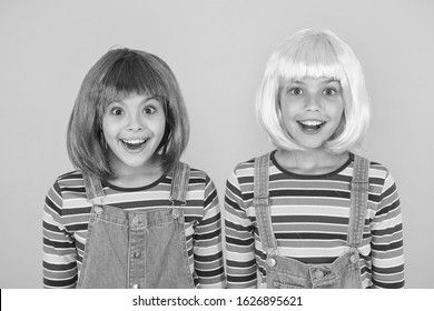 Cheerful friends in bright colorful wigs. Anime cosplay party concept. Happy childhood concept. Anime culture influence. Invitation for anime party. Happy little girls smiling faces. Anime fan.