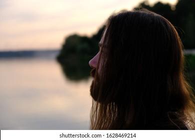 クローズアップ、日没の川で長く流れる髪を持つハンサムな白人のひげを生やした若い男の肖像画。絶望した男