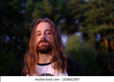 Close up, Portrait of a handsome Caucasian bearded young man with long flowing hair looking artistic at camera in the sunset river.