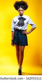 弓と格子縞のスカートと学校の制服の青いシャツの鼻ピアスを持つ美しい浅黒い肌のブルネットの少女の全身像。黄色のスタジオの背景に立っています