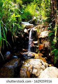 Foto eines Mini-Wasserfalls, der wie ein Teich aussieht Dieser Mini-Wasserfall stammt aus einem Fluss, der aus einem Wasserfall entstanden ist. Der Wasserfall heißt Curug Leuwi Hejo