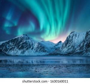 Aurora borealis über den schneebedeckten Bergen, der Küste des Sees und dem Spiegelbild im Wasser. Nordlichter über schneebedeckten Felsen. Winterlandschaft mit Polarlichtern, Fjord. Sternenhimmel mit heller Aurora