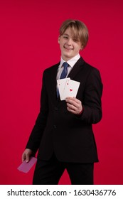 Teenager boy in a black jacket holds playing cards for poker and tricks in his hands and poses on a red background