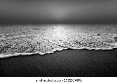 Wellen- und Sandstrand in Schwarz und Weiß. Ruhige Aussicht während des Sonnenuntergangs am Meer.