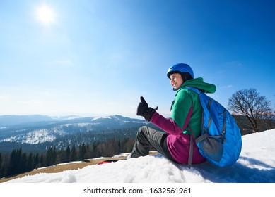Lächelnde weibliche Snowboarderin mit großem Rucksack, der auf schneebedecktem Gipfel ruht, zeigt Daumen hoch Geste auf Kopierraumhintergrund des blauen Himmels und der bewaldeten Berge. Extremer Wintersport, aktives Lifestyle-Konzept.