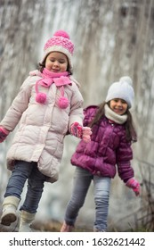 Two sweet little sisters walking between frozen trees during the winter cold day. They enjoying and have fun outdoor at the wintertime.