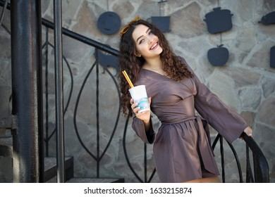 Stylish happy young woman with curly hair, dressed in a brown jumpsuit and yellow glasses, holds coffee in her hands to go.Portrait of a smiling brunette girl outdoors in spring