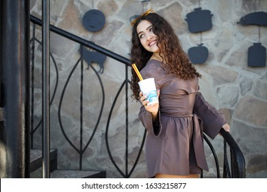 Stylish happy young woman with curly hair and a perfect smile dresses in a brown jumpsuit and yellow glasses, holds coffee in her hands to go. Portrait of a smiling girl outdoors