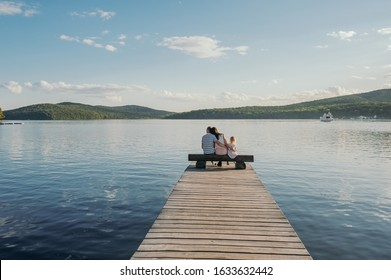 family happy vacation of parents with children, three people sitting back on a wooden pier on a Sunny summer day near the beautiful sea and clear sky, summer sea panorama with people