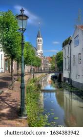 Farola tradicional, árboles, casas y una pequeña iglesia con torre a lo largo de un tranquilo canal en Amersfoort, Holanda