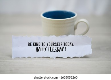 Inspirational quote - Be kind to yourself today. Happy Tuesday. With a cup of morning coffee and a white paper note concept on white wooden table background. Self notes and reminder motivational words