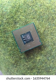 processor chip above the green grass. used as the central brain of a machine on a computer or PC