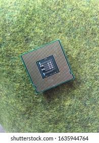 chip procesador por encima de la hierba verde. utilizado como el cerebro central de una máquina en una computadora o PC