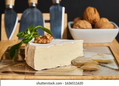 Nahaufnahme von Käse und Walnüssen auf Holzkäsebrett