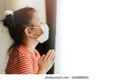Weinig Chinees meisje dat masker draagt ter bescherming van pm2.5 en coronavirus Covid-19. Blijf thuis biddend tot God. Online kerkverering in zondag. Weinig Aziatisch meisje hand bidden thuis. Sociale afstand nemen.