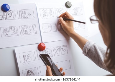 Woman draws a storyboard for an animated film on a white board.