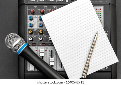 Notepad with audio sound mixer and microphone on black. Top view. Space for text.