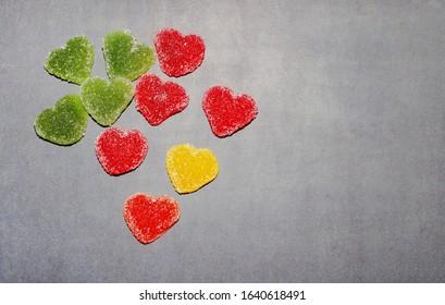 暗い黒板背景にハートの形をした色とりどりのマーマレードのお菓子。マーマレードマルチカラーのお菓子、分離。鉱山スペース、バレンタインデー、子供用デザート