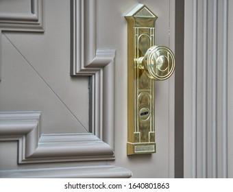 Pomo o tirador de puerta de acero inoxidable en puerta de madera con hermosa iluminación.