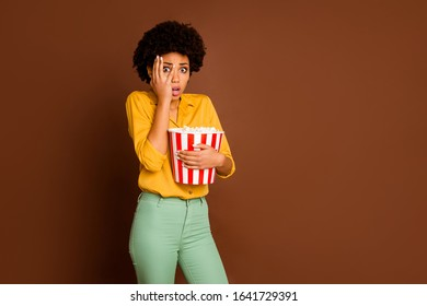 Photo of frightened dark skin wavy lady hold popcorn bucket eat corns watch scary movie thriller hide eye terrified wear yellow shirt green pants isolated brown color background