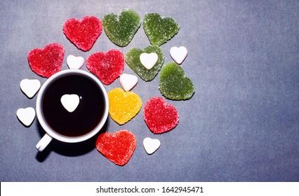 ホットチョコレートとハートゼリーキャンディーの朝食。青色の背景にハートの形でマルチカラーのマーマレードとコーヒーのカップ。鉱山空間、上面図、バレンタインデー、愛。
