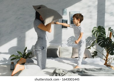 Mommy and son laughing and playing on the bed, having a pillow fight in the morning while wearing pajamas. Family casual lifestyle series.